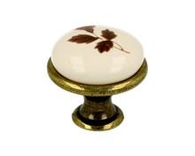 Stylizowana gałka metalowa z wierzchołkiem porcelanowym, doskonała do kuchni lub łazienki.  Pokrycie galwaniczne - mosiądz antyczny Kolor porcelany -...