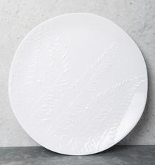 Ceramiczny talerz w kolorze białym z wytłoczonym wzorem liści.To zaproszenie by cieszyć się wolnością i czerpać ze źródeł natury. Produkty marki...