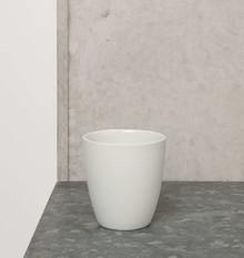 Porcelanowy kubeczek w kolorze białym. Produkty marki Urban Nature Culture łączą w sobie wpływy i surowce z całego świata, w tym drewno mango,...