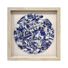 Okrąg z niebieskiej i białej porcelany w ramce na bawełnianym tle